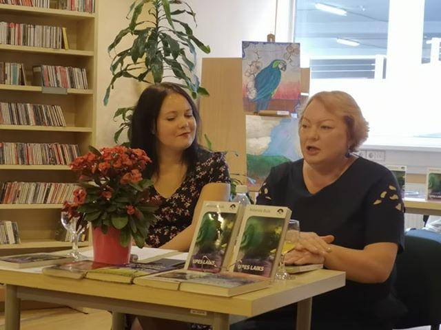 Pasākuma moderatore, RCB galvenā bibliotekāre Evita Hofmane sarunā ar rakstnieci Rolandu Bulu